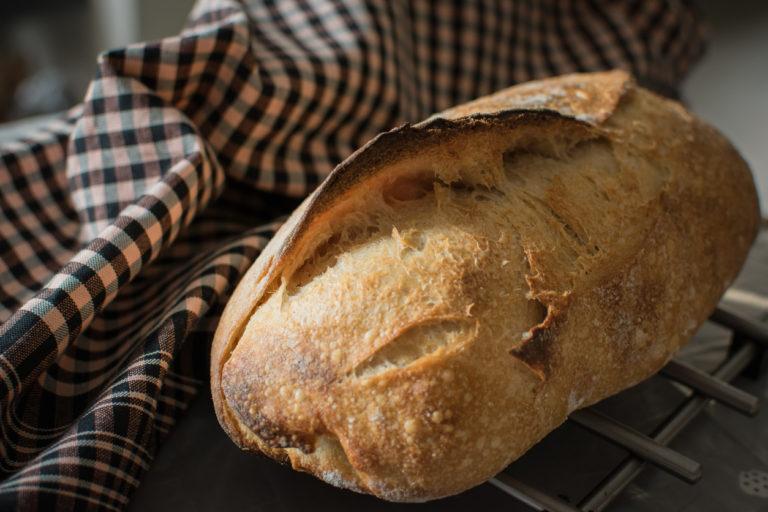 Nybakt speltbrød i et kjøkkenhåndkle