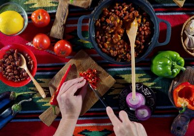 Et par hender som lager chili sin karne. Det er et bord full av mat med en gryte med chili sin carne i midten av bordet.