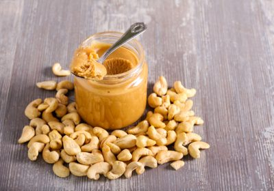 Cashew butter spread in a jar and cashew near on the table