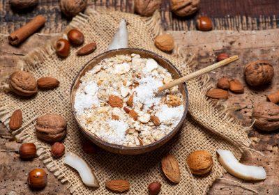 En bolle med havregrøt på et bord omringet av nøtter, kokos og kanel